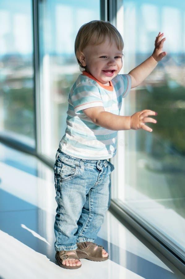 Bebê feliz perto da janela grande imagens de stock royalty free