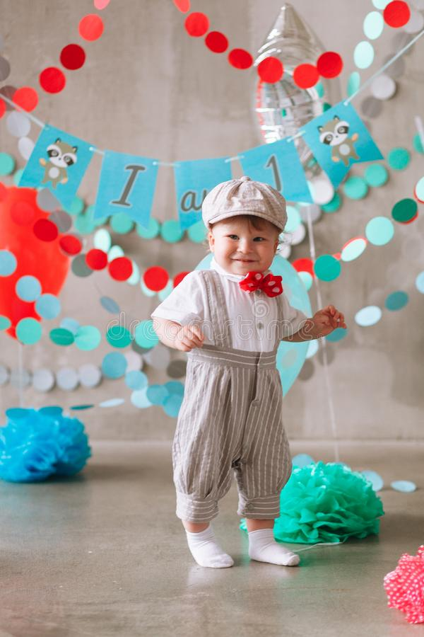 Bebê feliz que comemora o primeiro aniversário Festa de anos das crianças decorada com balões e a bandeira colorida fotos de stock royalty free