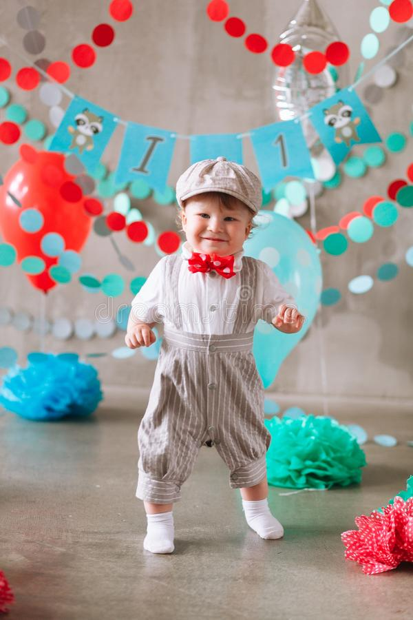 Bebê feliz que comemora o primeiro aniversário Festa de anos das crianças decorada com balões e a bandeira colorida imagens de stock