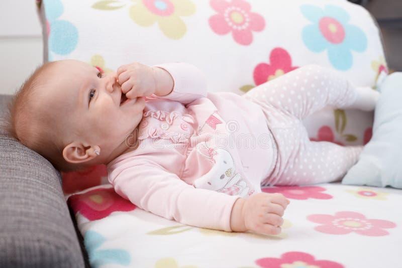 Bebê feliz que encontra-se no sofá foto de stock royalty free