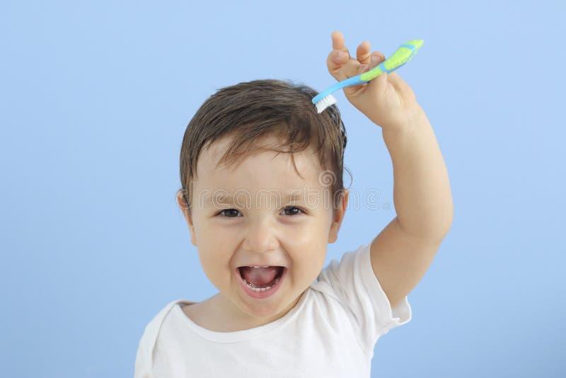 Bebê feliz que guarda uma escova de dentes em uma mão fotos de stock royalty free