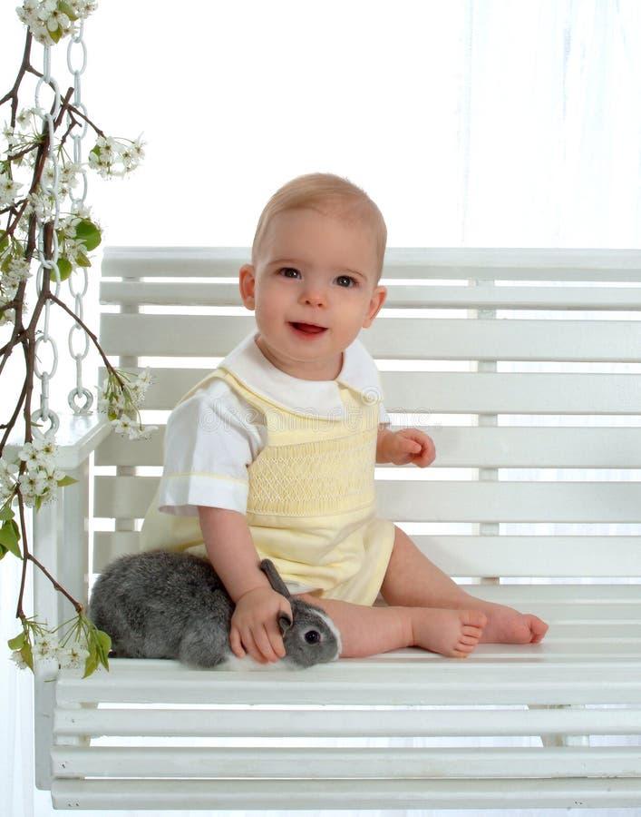Bebê feliz que Petting o coelho fotografia de stock royalty free