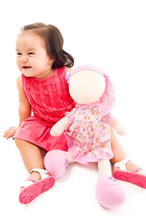 Bebê feliz que prende uma boneca fotografia de stock royalty free