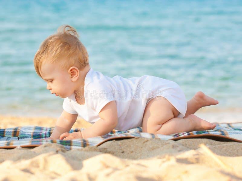 Bebê feliz que rasteja na praia fotos de stock royalty free