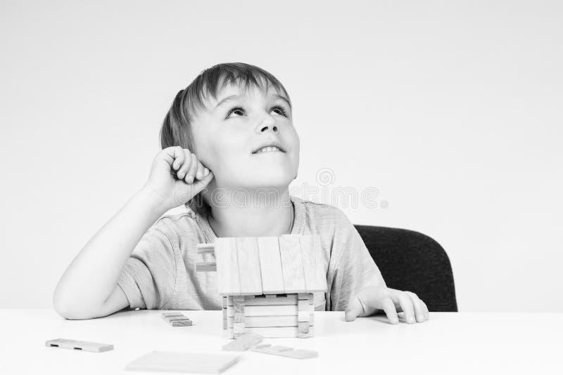 Bebê feliz que sonha sobre sua própria casa O rapaz pequeno constrói a casa de madeira pequena na tabela Criança que joga com blo foto de stock