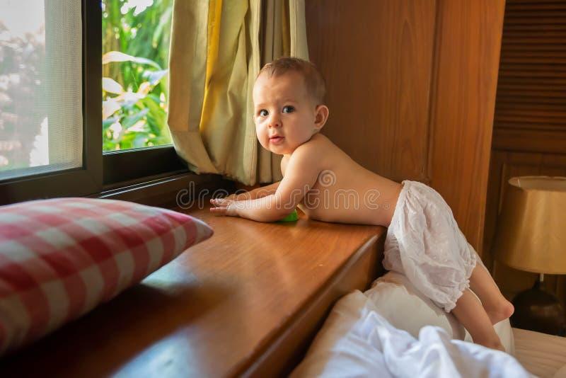 Bebê idoso pequeno feliz e pensativo de oito meses que pendura no peitoril da janela fotografia de stock