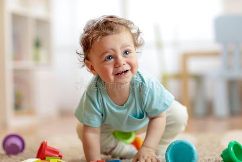 Bebê infantil bonito que rasteja no assoalho em casa, jogando com brinquedos coloridos fotos de stock