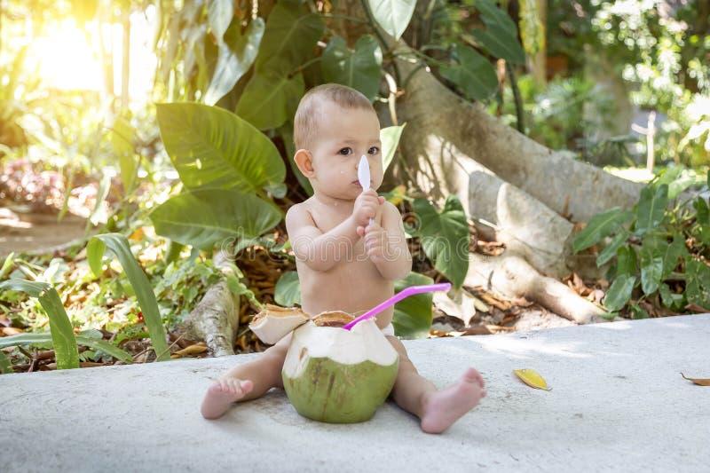 Bebê infantil triste em férias tropicais Come e bebe o coco novo verde Senta-se em uma terra e guardam-se uma colher Selvas sobre foto de stock royalty free