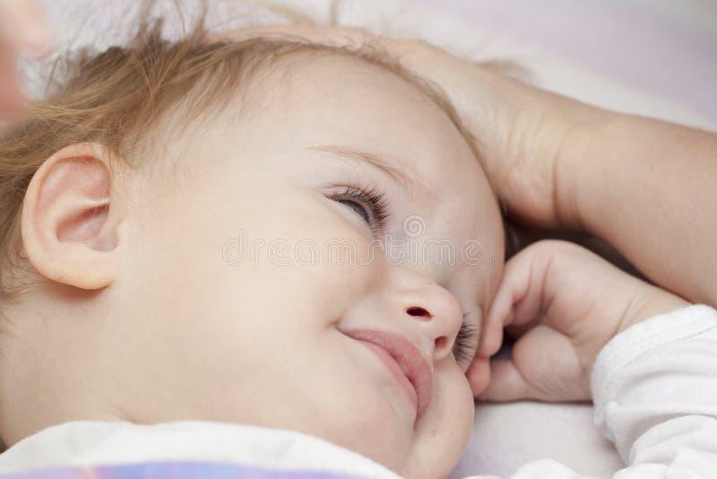 Bebê infeliz na cama fotos de stock royalty free