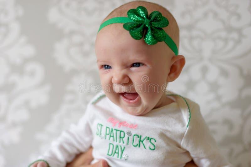 Bebê irlandês com os olhos azuis que vestem o equipamento do dia do ` s de St Patrick fotografia de stock