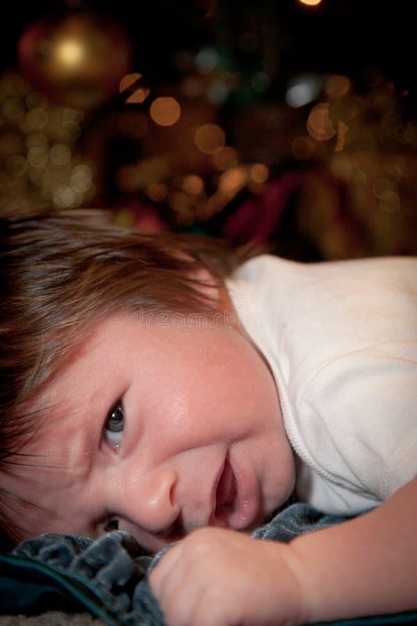 Bebê irritado no tempo da cama foto de stock