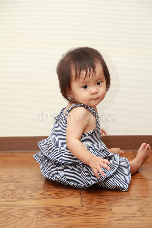 Bebê japonês que senta-se no assoalho imagem de stock