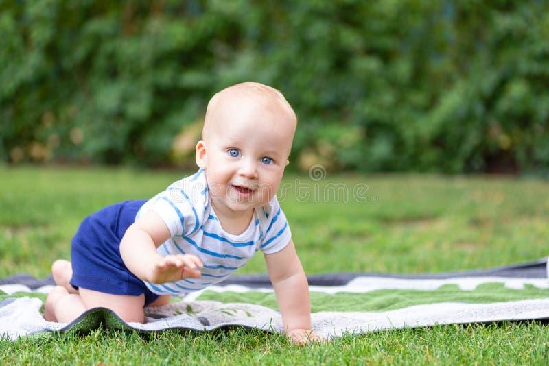Bebê louro pequeno bonito que rasteja na grama verde fresca Caçoe ter o divertimento que faz primeiras etapas no gramado natural  foto de stock