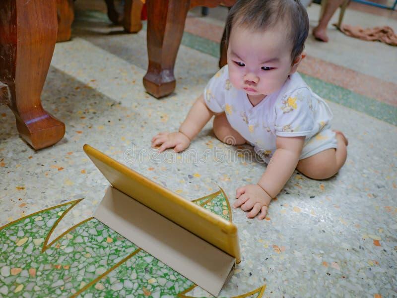 Bebê masculino asiático de Cutie muito sério e olhar na tabuleta fotografia de stock