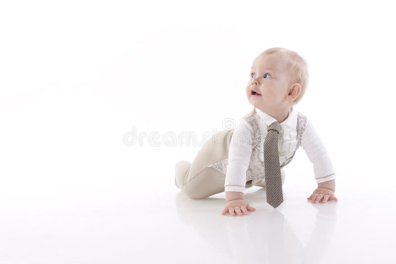 Bebê-menino de sorriso em um rastejamento do terno do romper foto de stock royalty free