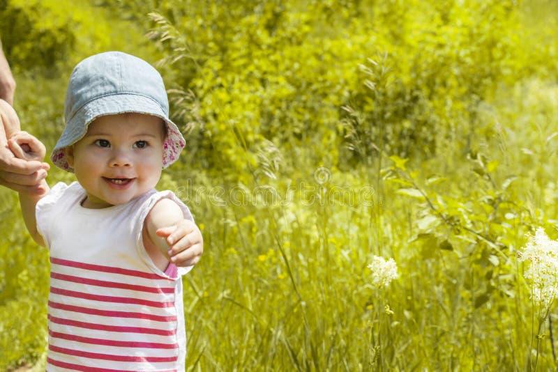 Bebê 11 meses que sorriem mostrando os dentes e puxando a mão para a frente imagem de stock