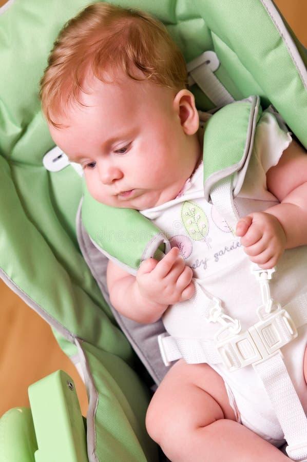Bebê na cadeira de alimentação elevada imagem de stock
