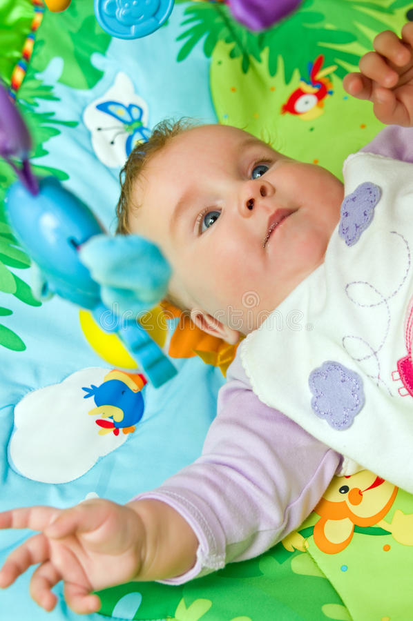 Bebê na esteira colorida foto de stock