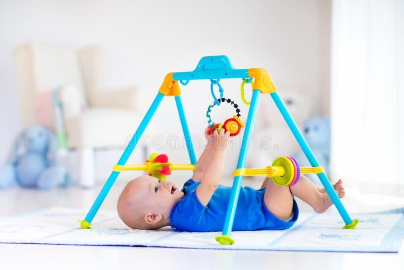 Bebê na esteira do jogo Criança que joga no gym imagem de stock
