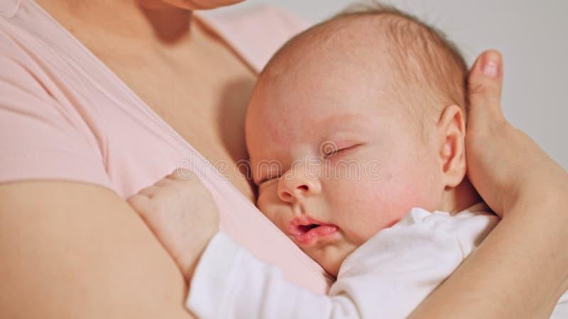 Bebê na queda dos braços das mães adormecida foto de stock royalty free