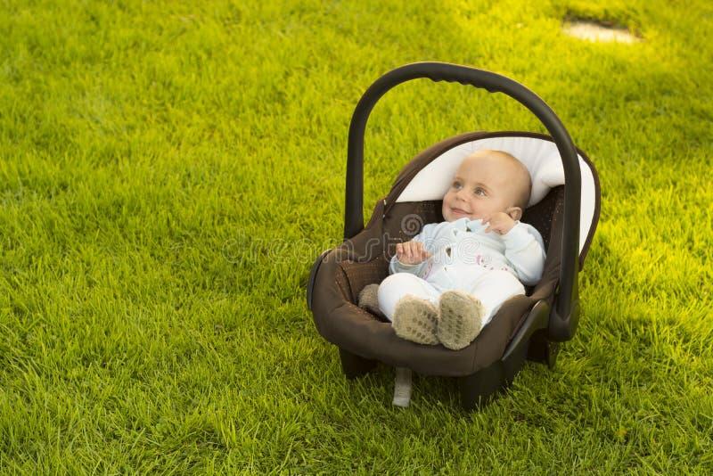 Bebê no banco de carro na grama fotos de stock royalty free