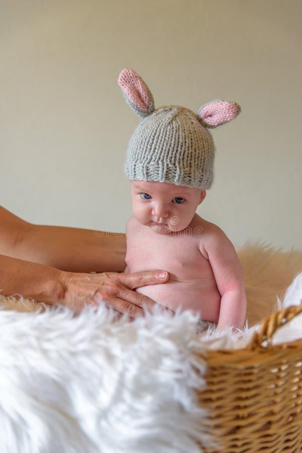 Bebê no chapéu da orelha do coelho que senta-se na cesta para o retrato da Páscoa imagens de stock