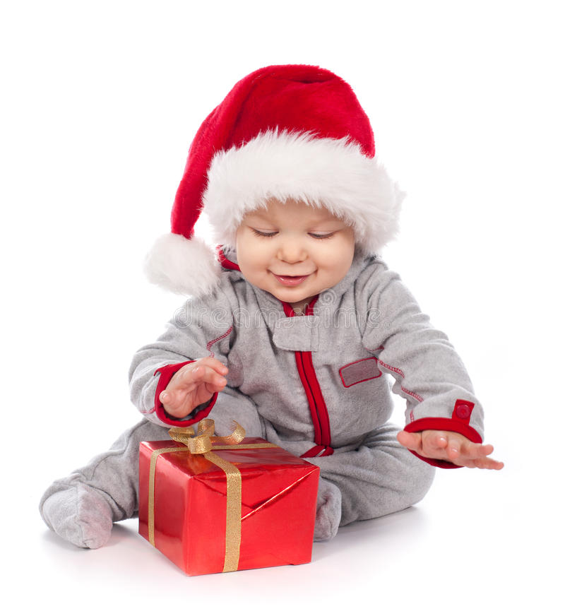 Bebê no chapéu de Santa que joga com a caixa de presente do Natal fotos de stock