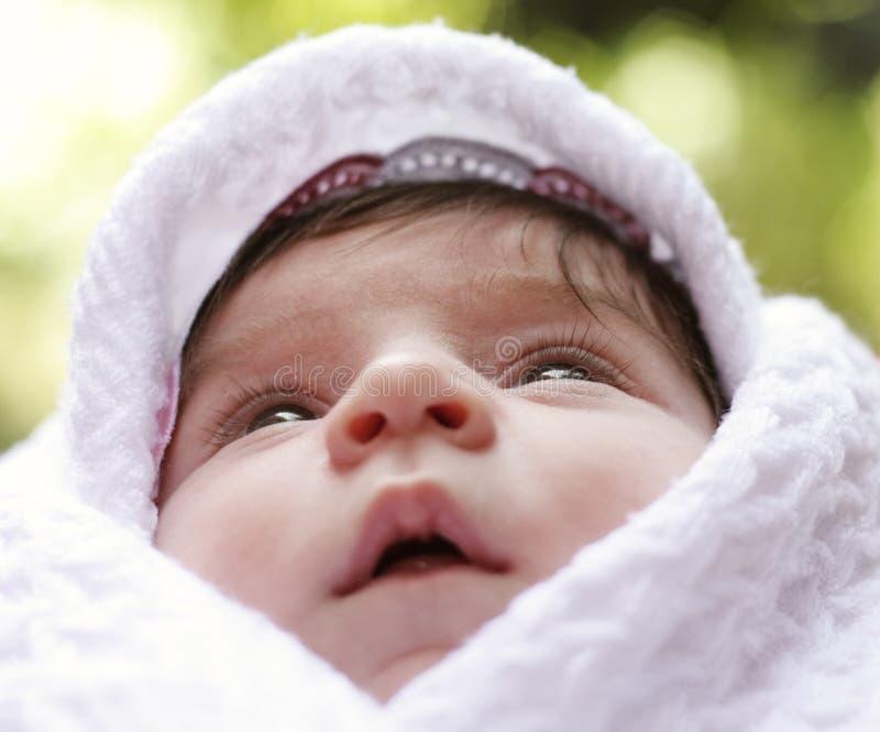 Bebê no coverlet que olha acima imagem de stock