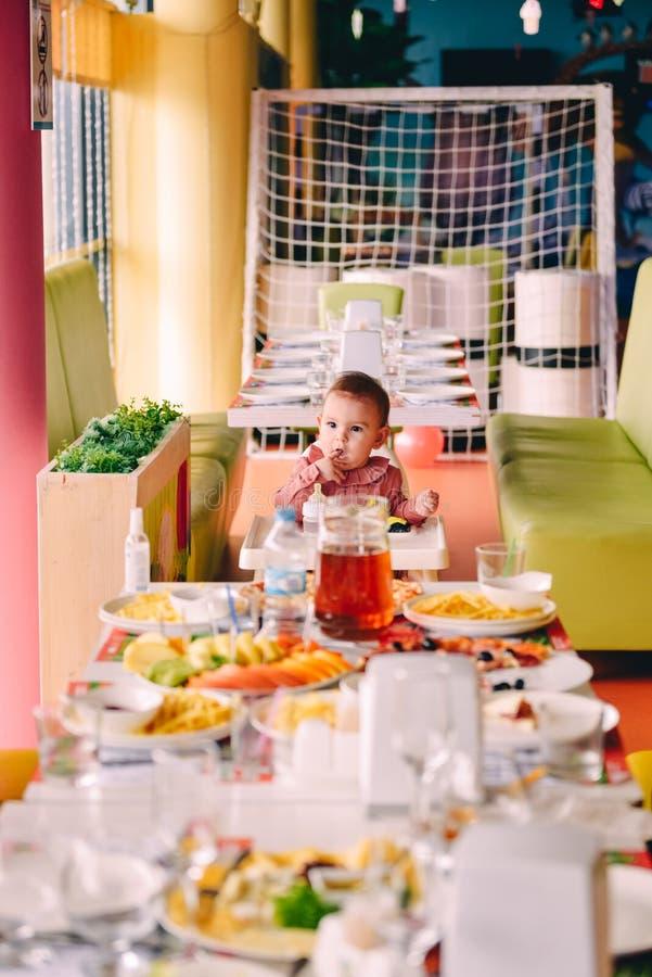 Bebê no rosa no cadeirão na frente da tabela grande do fest na festa de anos foto de stock royalty free