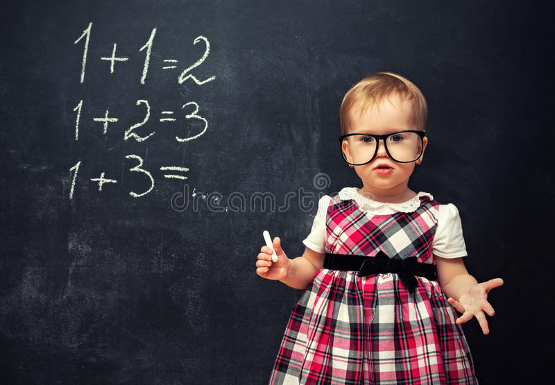 Bebê nos vidros e giz em uma administração da escola com arithmeti fotografia de stock