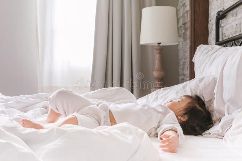 Bebê novo 2-3 anos que dormem na cama na manhã fotos de stock royalty free