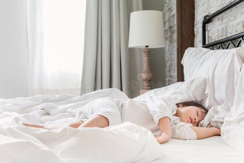 Bebê novo 2-3 anos que dormem na cama na manhã foto de stock