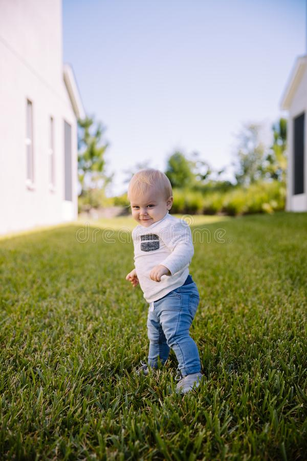 Bebê novo bonito e adorável da criança que joga na grama de verde do quintal e que sorri na câmera fotos de stock royalty free