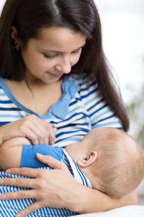 Bebê novo da terra arrendada da matriz Criança dos cuidados da mamã Mulher que amamenta a criança recém-nascida fotos de stock