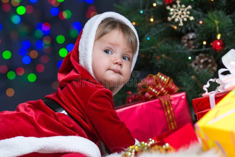 Bebê Papai Noel perto da árvore de Natal com presentes imagens de stock royalty free