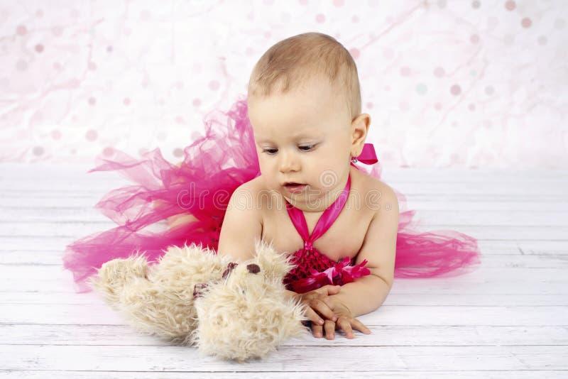 Bebê pequeno adorável que encontra-se no assoalho com urso de peluche fotos de stock