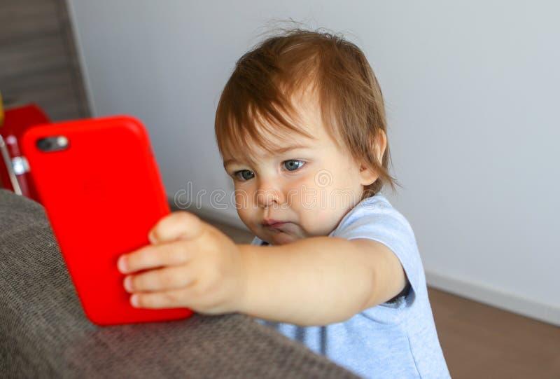 Bebê pequeno adorável que olha seriamente na tela do telefone celular fotos de stock