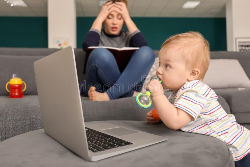 Bebê pequeno bonito com o portátil com mãe cansado em casa fotos de stock