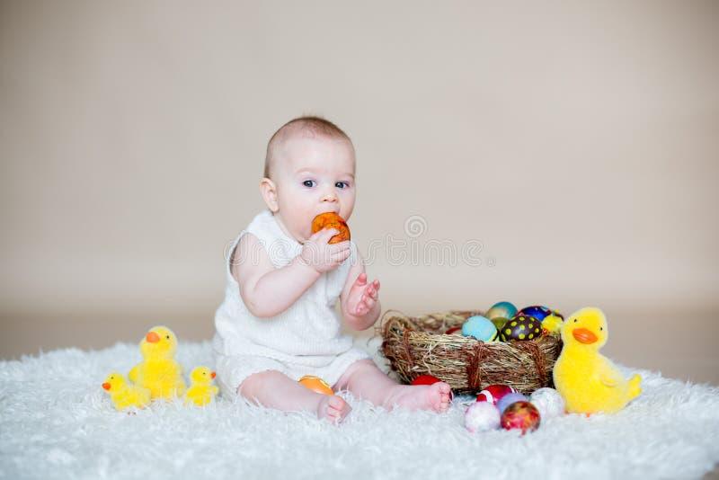 Bebê pequeno bonito da criança, jogando com ovos da páscoa coloridos imagem de stock royalty free