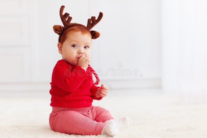 Bebê pequeno bonito do ruivo com o christma do gosto da faixa da rena foto de stock