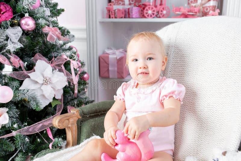 Bebê pequeno bonito em presentes da cadeira e do Natal do vintage Criança pequena que tem o divertimento perto da árvore de Natal fotografia de stock royalty free