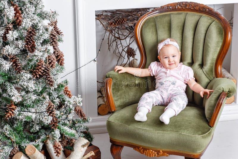 Bebê pequeno bonito em presentes da cadeira e do Natal do vintage Criança pequena que tem o divertimento perto da árvore de Natal imagem de stock