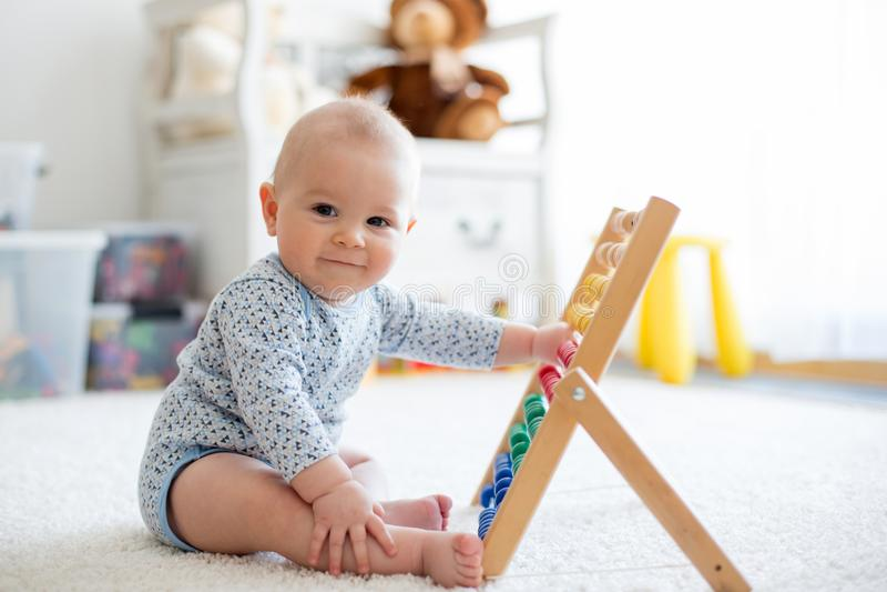 Bebê pequeno bonito, jogando com ábaco em casa foto de stock