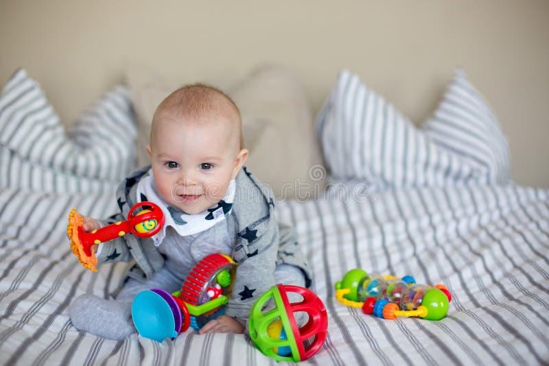 Bebê pequeno bonito, jogando em casa na cama com lotes do colorf imagens de stock royalty free