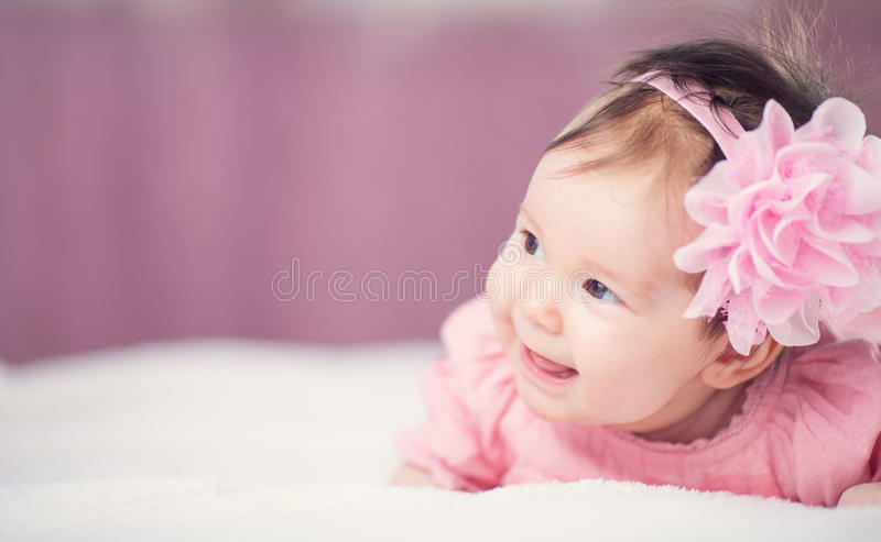 Bebê pequeno bonito que encontra-se na cama no vestido cor-de-rosa imagens de stock royalty free