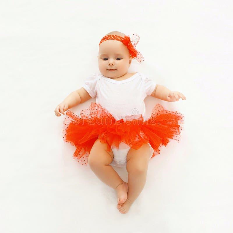Bebê pequeno bonito que encontra-se na saia vermelha foto de stock royalty free