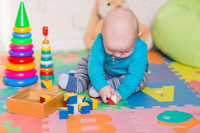 Bebê pequeno bonito que joga com brinquedos coloridos imagem de stock royalty free