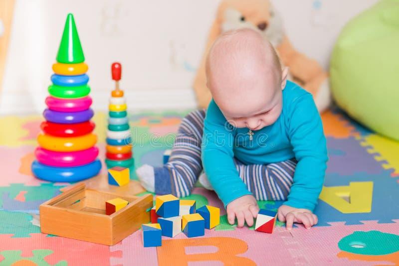 Bebê pequeno bonito que joga com brinquedos coloridos foto de stock royalty free