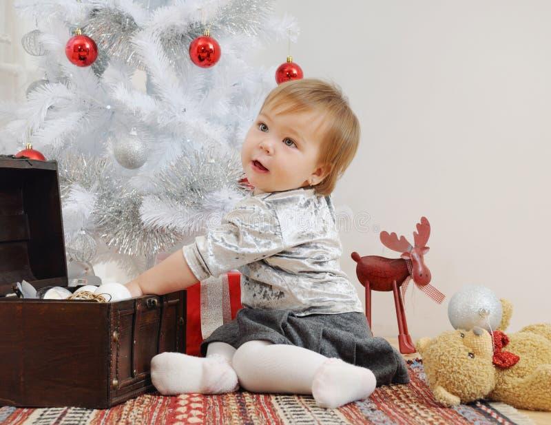 Bebê pequeno bonito que joga com brinquedos do Natal fotos de stock royalty free