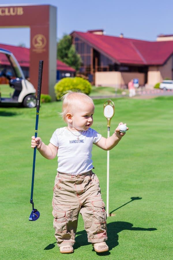 Bebê pequeno bonito que joga o golfe em um campo foto de stock royalty free